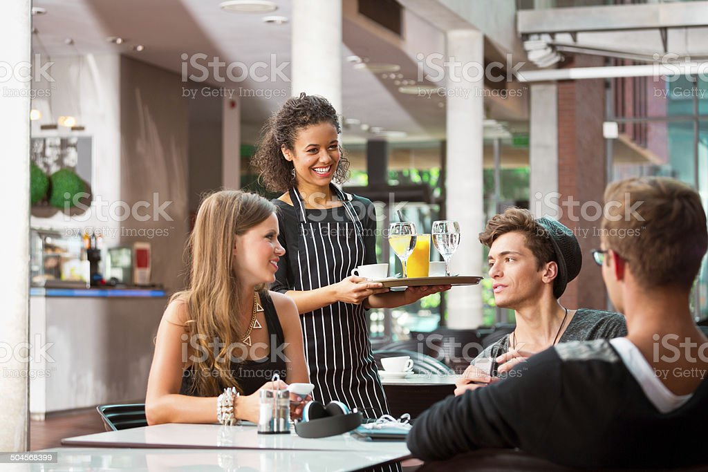Cheerful waiter serving drinks Cheerful young female waiter serving drinks for young people in cafe. 20-24 Years Stock Photo