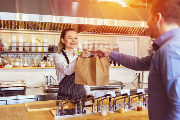 cheerful waitress wearing apron serving customer at counter in restaurant - small business and service concept with young woman owner giving eco friendly paper bag with take away food to online client - food delivery стоковые фото и изображения