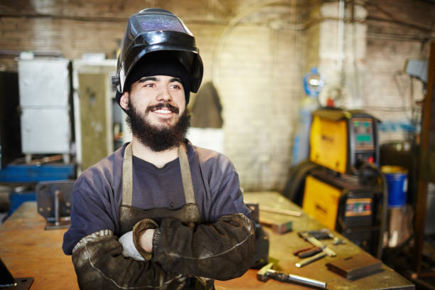 Cheerful welder dreaming of own production stock photo