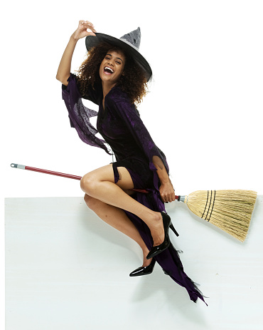istock Cheerful witch pretending to sit on a broom 513901021