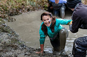 Happy mature woman being pulled from dirty pool on cross country run, determination, achievement, success