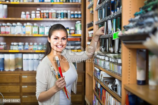 594918592 istock photo Cheerful woman choosing various color in tube 594918592