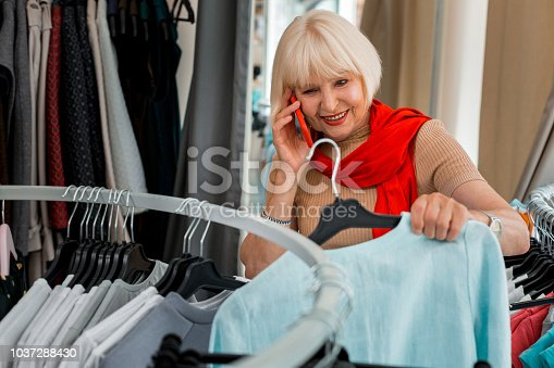 istock Cheerful woman consulting her friend concerning a purchase in clothing store 1037288430