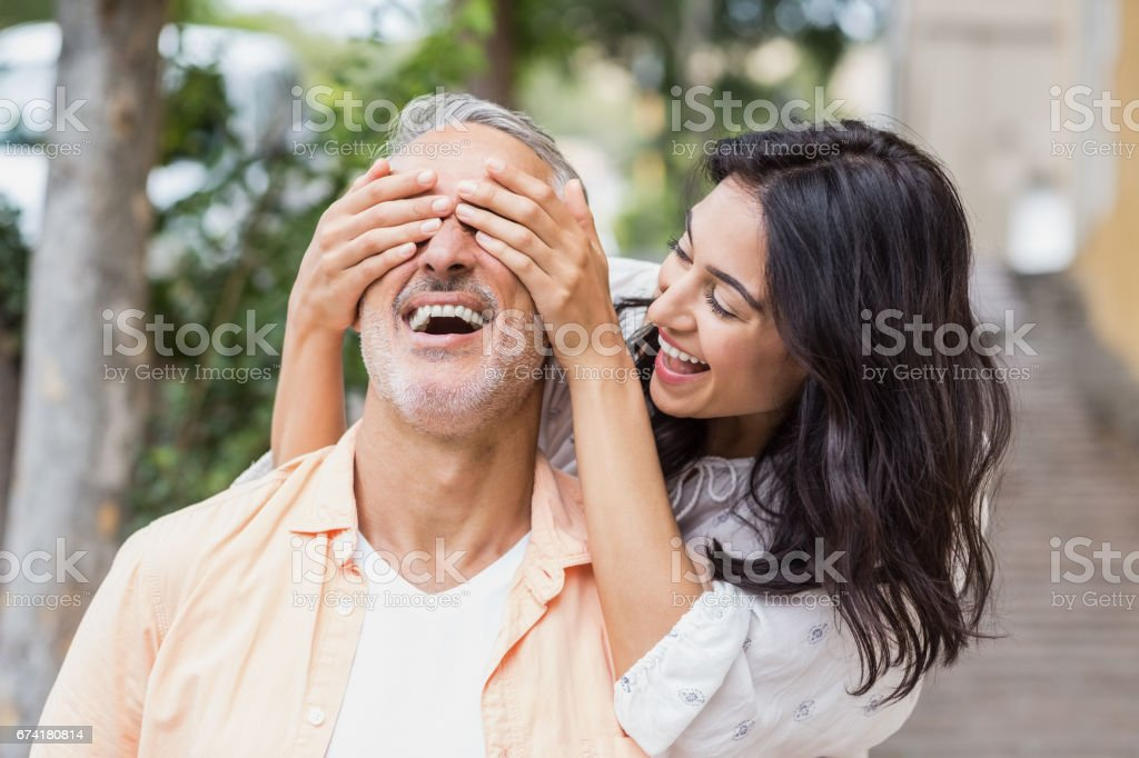 Cheerful woman covering eyes of man stock photo