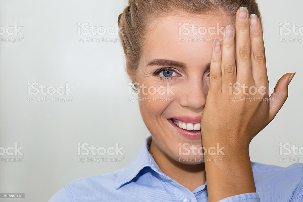Cheerful woman covering half of face with hand stock photo