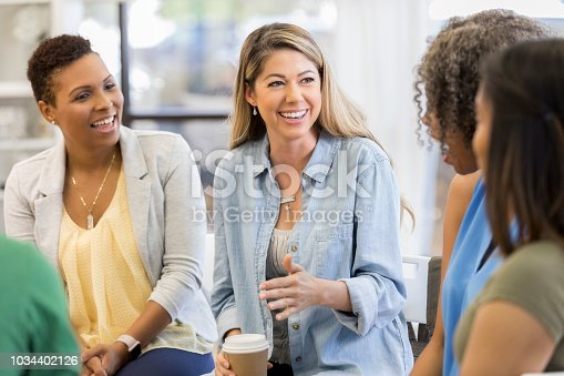 1055095320 istock photo Cheerful woman discusses something with friends 1034402126
