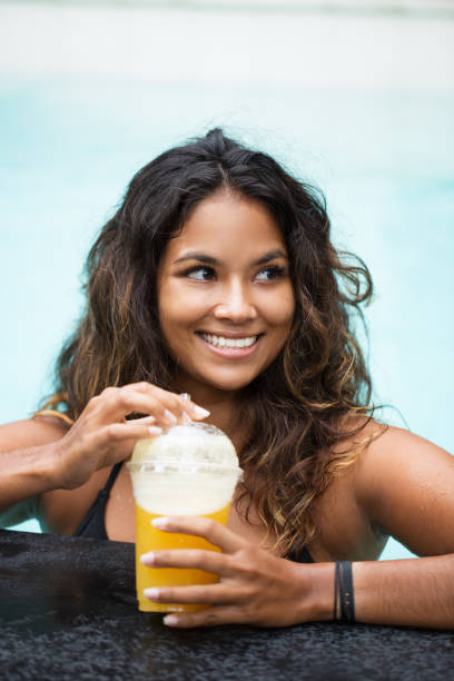 Cheerful woman drinking cocktail in swimming pool stock photo