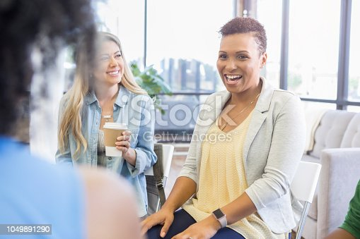 1055095320 istock photo Cheerful woman during support group session 1049891290