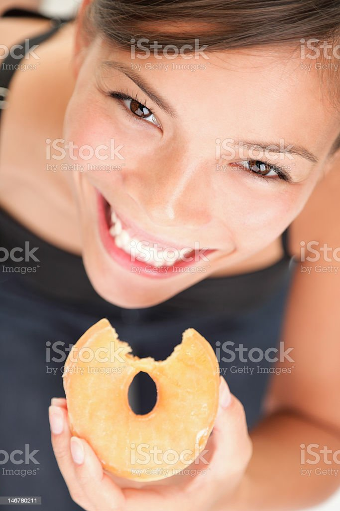Cheerful woman eating donut - junk food serie royalty-free stock photo