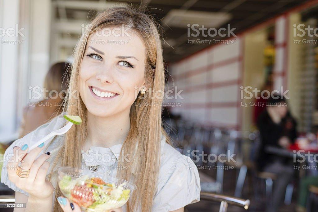 Alegre mujer comiendo ensalada en el cafe foto de stock libre de derechos