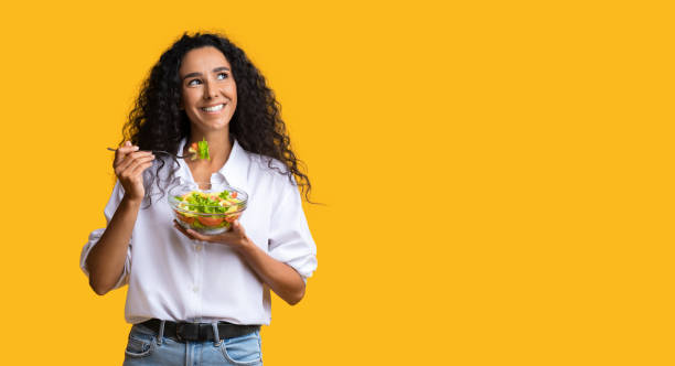 Cheerful Woman Eating Vegetable Salad From Bowl And Looking At Copy Space stock photo