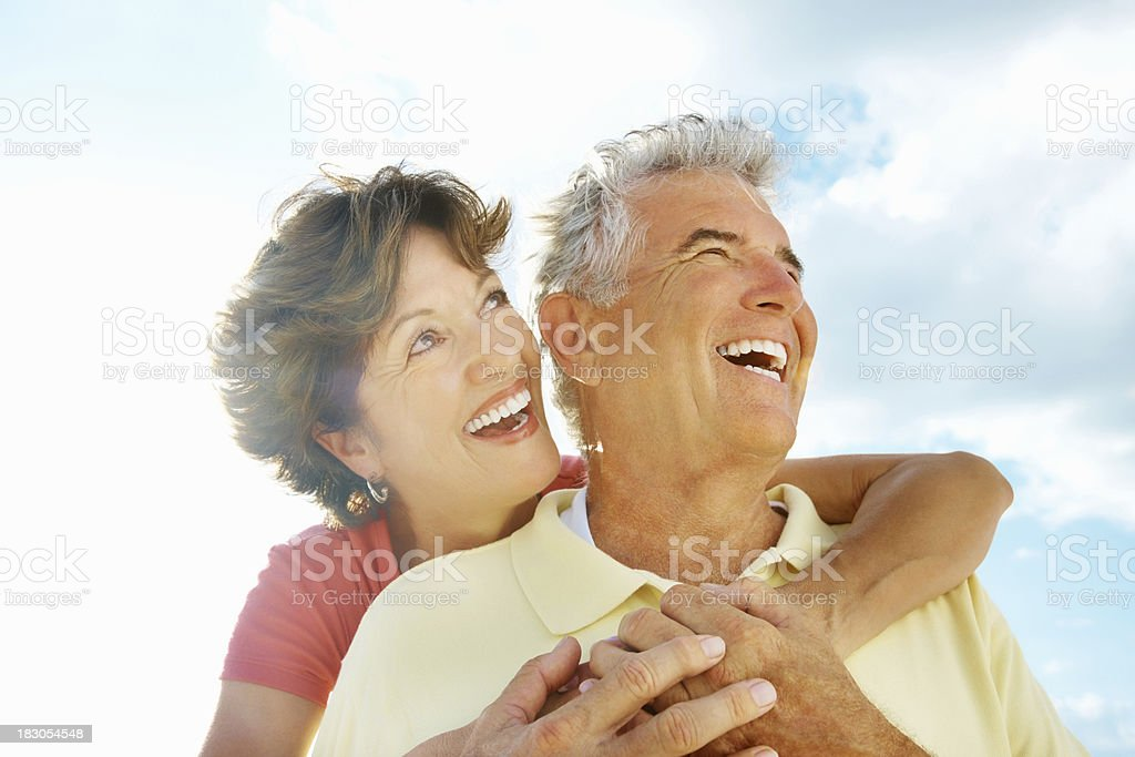 Cheerful woman embracing a senior man from behind against sky royalty-free stock photo