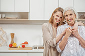 istock Cheerful woman embracing her senior parent in kitchen 660471666