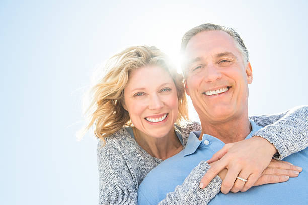 cheerful woman embracing man from behind against sky - wife stock photos and pictures