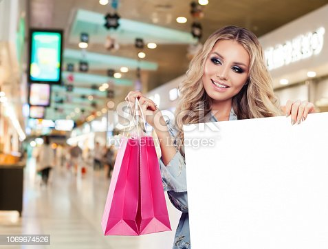 Cheerful woman fashion model with empty paper board and shopping bags in shopping mall background