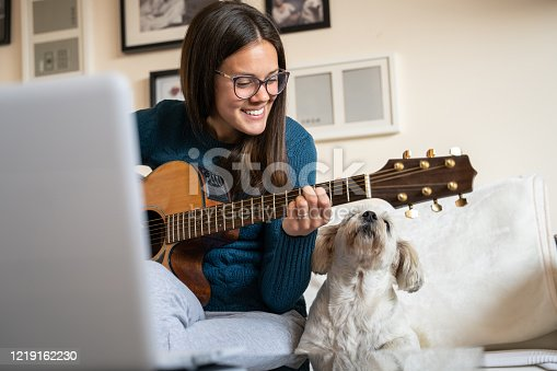 Cheerful Woman Filming Herself Playing Acoustic Guitar with her Playful Puppy