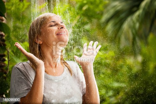 Woman wearing a gray T-shirt is having a shower in the tropical surroundings. She is wet.   url=http://www.istockphoto.com/search/lightbox/9786750]
