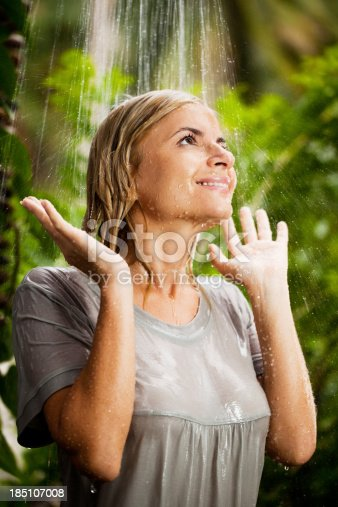Woman wearing a gray T-shirt is having a shower in the tropical surroundings. She is wet and looking up.