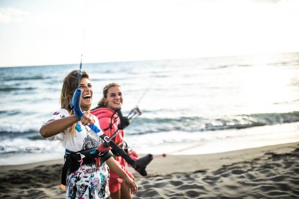 fröhliche frau, die spaß vor dem kitesurfen mit ihrem freund hat. - kitesurfen lernen stock-fotos und bilder