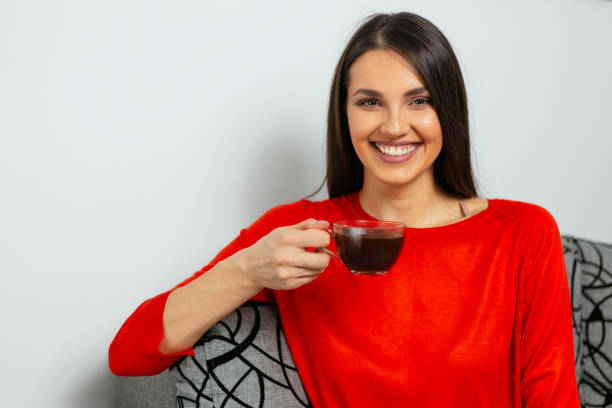Cheerful woman holding cup of coffee and smiling stock photo