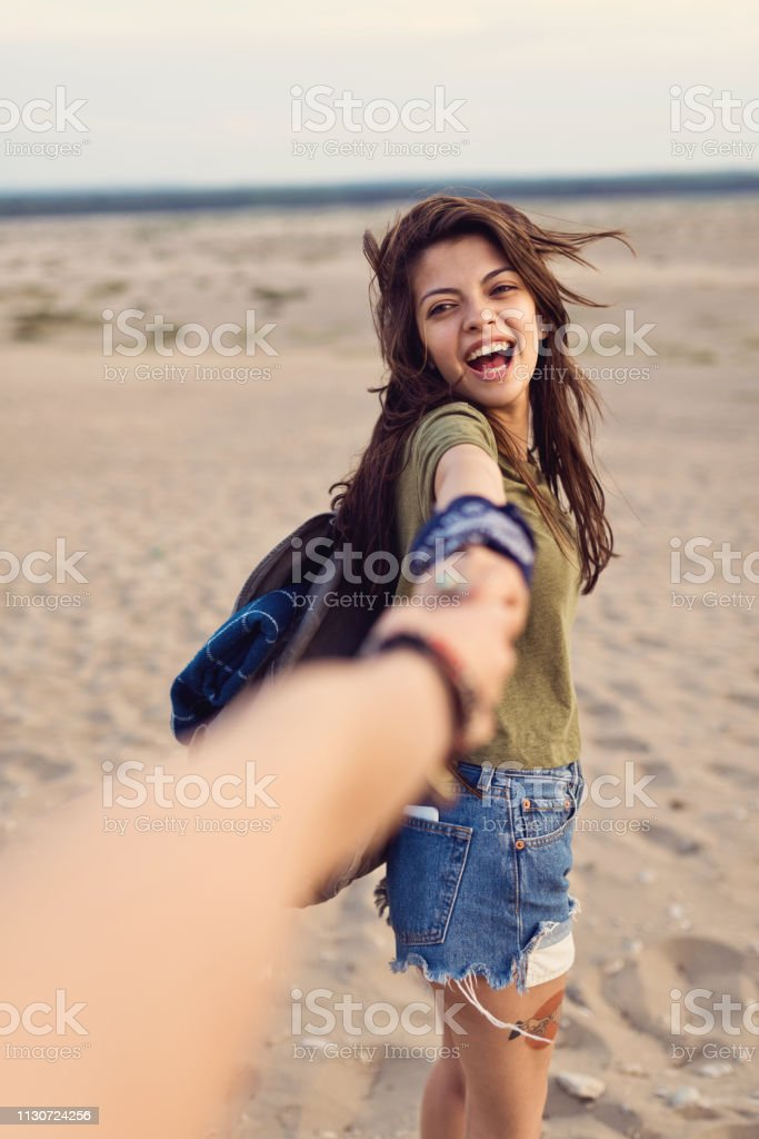 Cheerful woman holding friend's hand in desert Cheerful young woman holding friend's hand. Female backpackers are enjoying hiking in desert. Hipsters are spending leisure time together. 20-24 Years Stock Photo