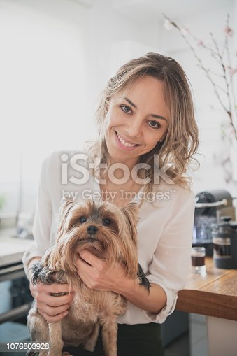 Close up of woman petting her dog in kitchen and smiling, animal portrait, affection