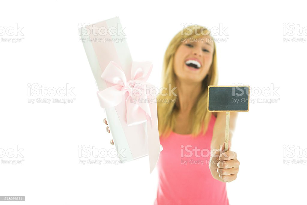 Cheerful woman holding pink gift and blackboard stock photo