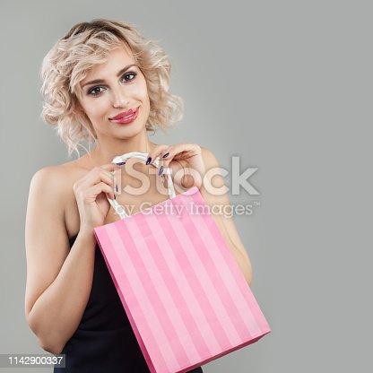 Cheerful woman holding shopping bag