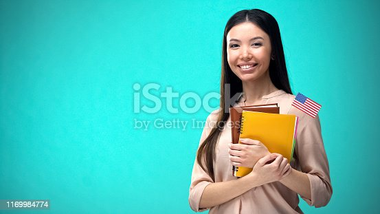 Cheerful woman holding USA flag book, education abroad, learning language