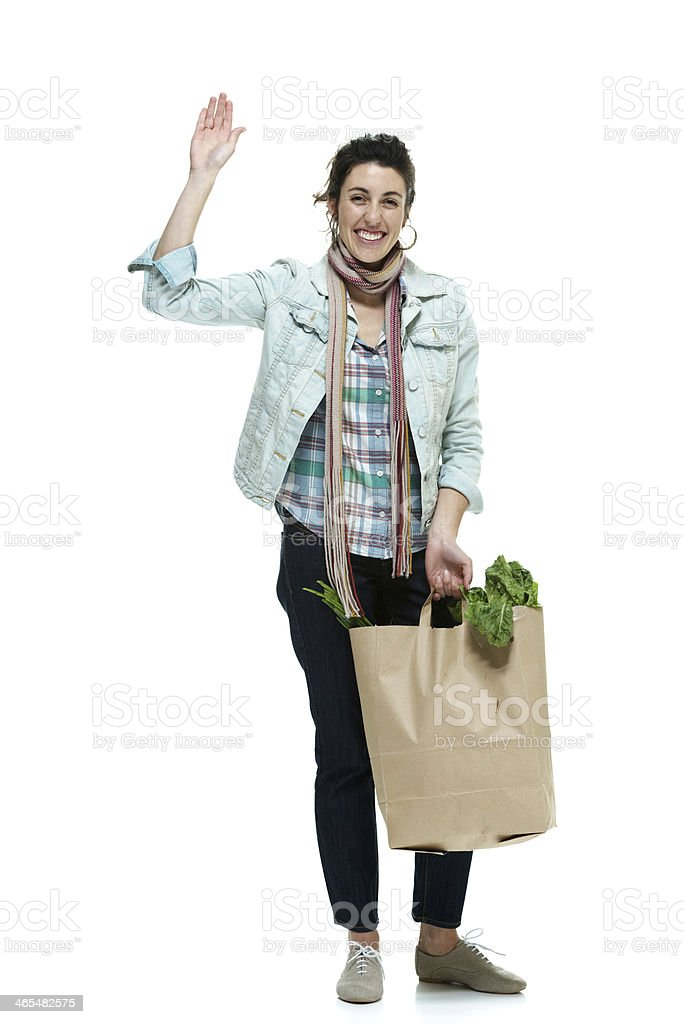 Cheerful woman holding vegetable bag and waving hand royalty-free stock photo