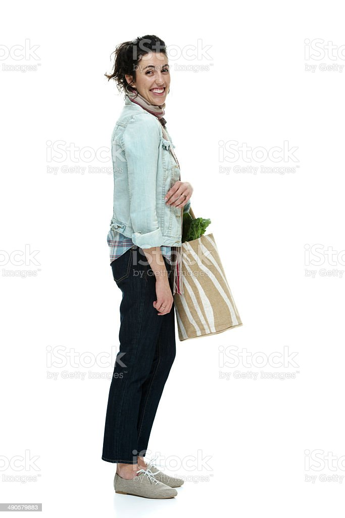 Cheerful woman holding vegetable bag royalty-free stock photo