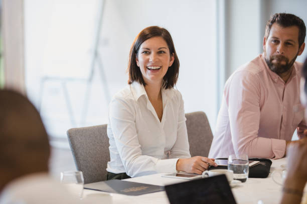 Cheerful woman in business meeting with colleagues stock photo