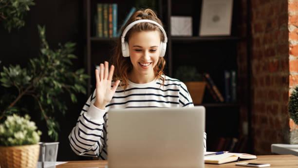 Fröhliche Frau in Kopfhörer gruß Freund, während sprechen auf Laptop zu Hause – Foto