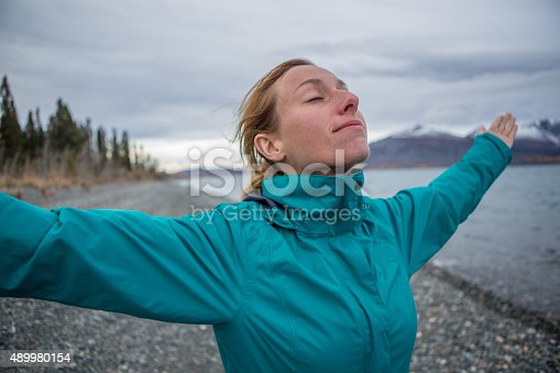 istock Cheerful woman in nature arms outstretched for freedom 489980154