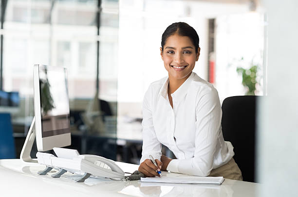 cheerful woman in office - receptionist stock photos and pictures