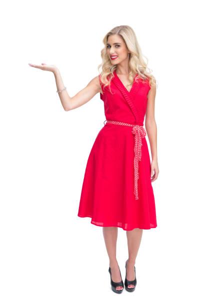 stets gut gelaunte frau im roten kleid präsentieren etwas in der hand - wickelkleid lang stock-fotos und bilder