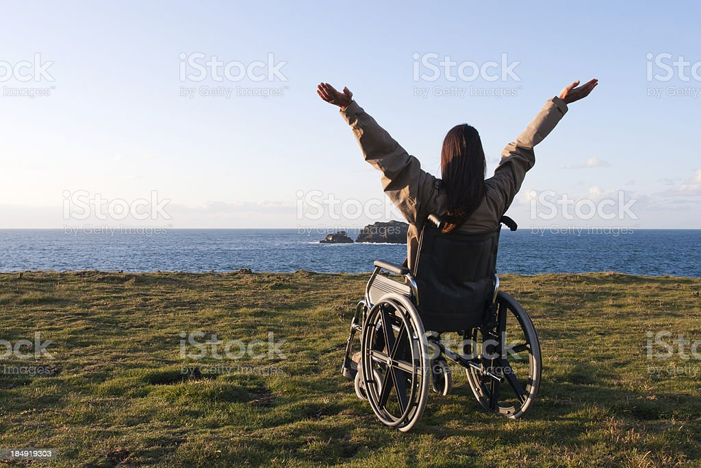Cheerful woman in wheelchair arms up by the sea. stock photo