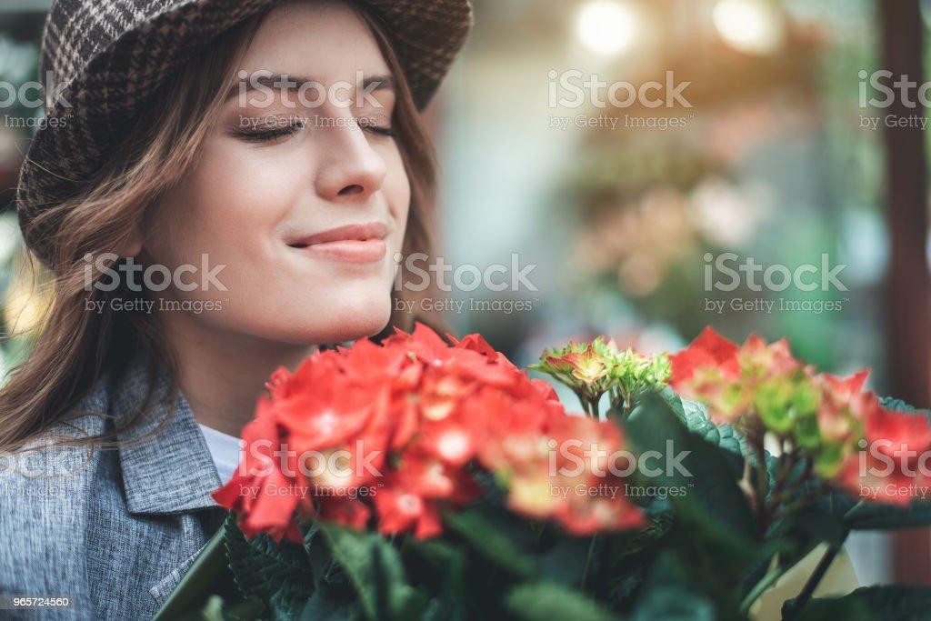 Cheerful woman is enjoying flower aroma outside stock photo