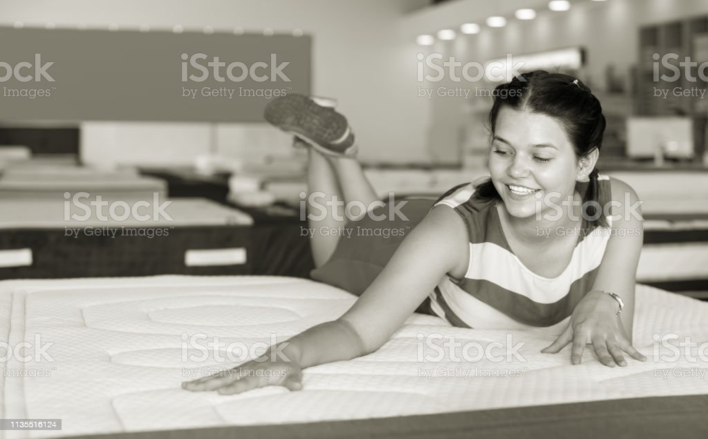 cheerful woman is lying on bed and testing mattress for relax in the...