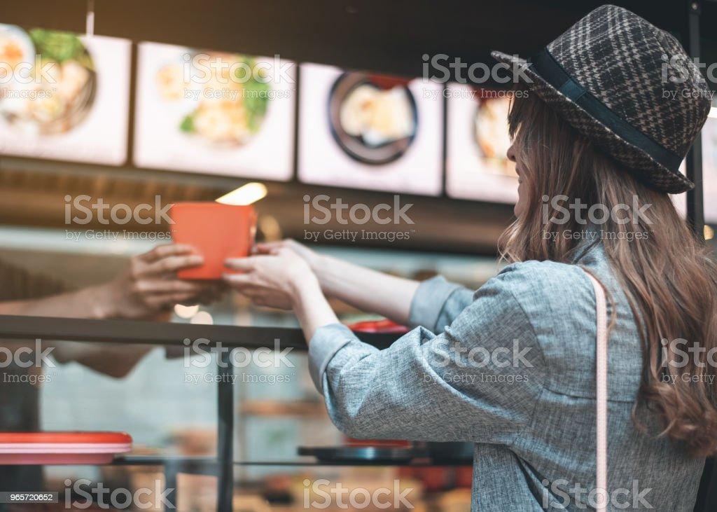Cheerful woman is receiving order in cafe - Стоковые фото Азиатского и индийского происхождения роялти-фри