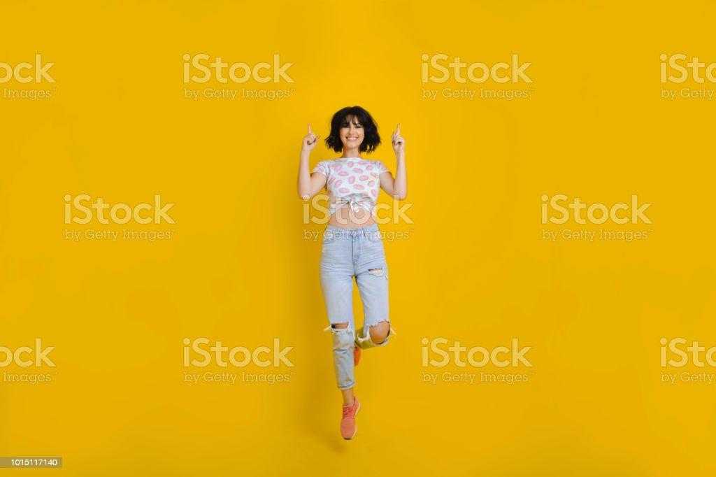 Femme joyeuse sautant et pointant vers le haut photo libre de droits