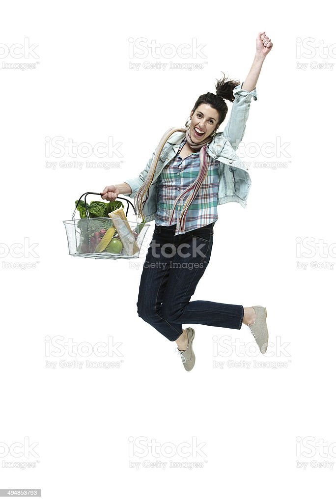 Cheerful woman jumping & holding vegetable basket royalty-free stock photo
