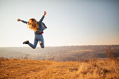 Cheerful young woman jumping in the park