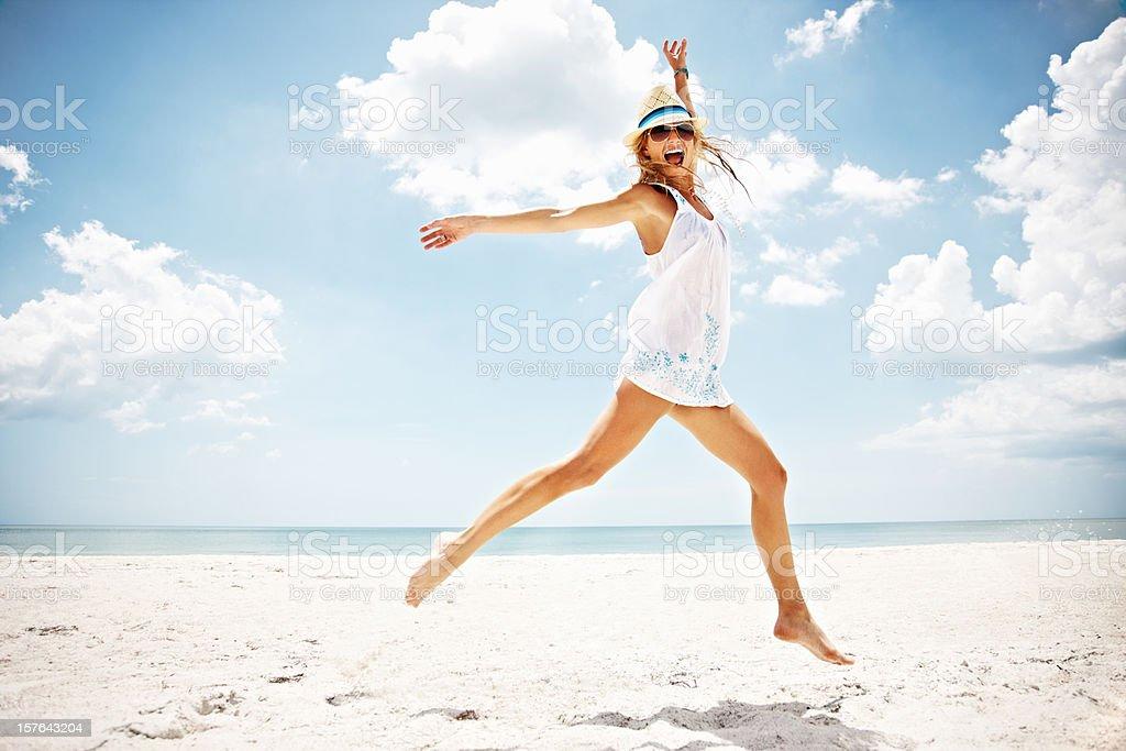 Joyeuse femme sautant sur la plage - Photo