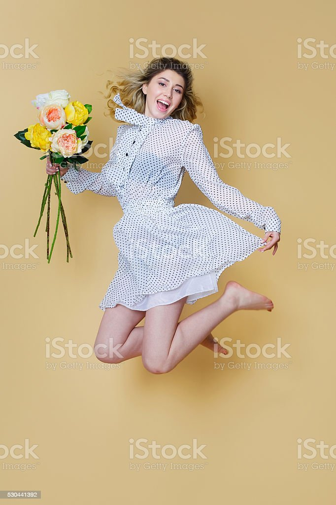 Cheerful woman jumping with flowers bouquet stock photo