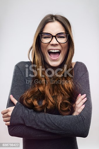 Cheerful young woman laughing against white background. Beautiful female with long brown hair is standing arms crossed. She is wearing casuals and eyeglasses. Vertical studio photography from a DSLR camera. Sharp focus on eyes.