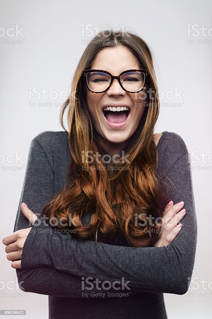 Cheerful woman laughing against white background stock photo