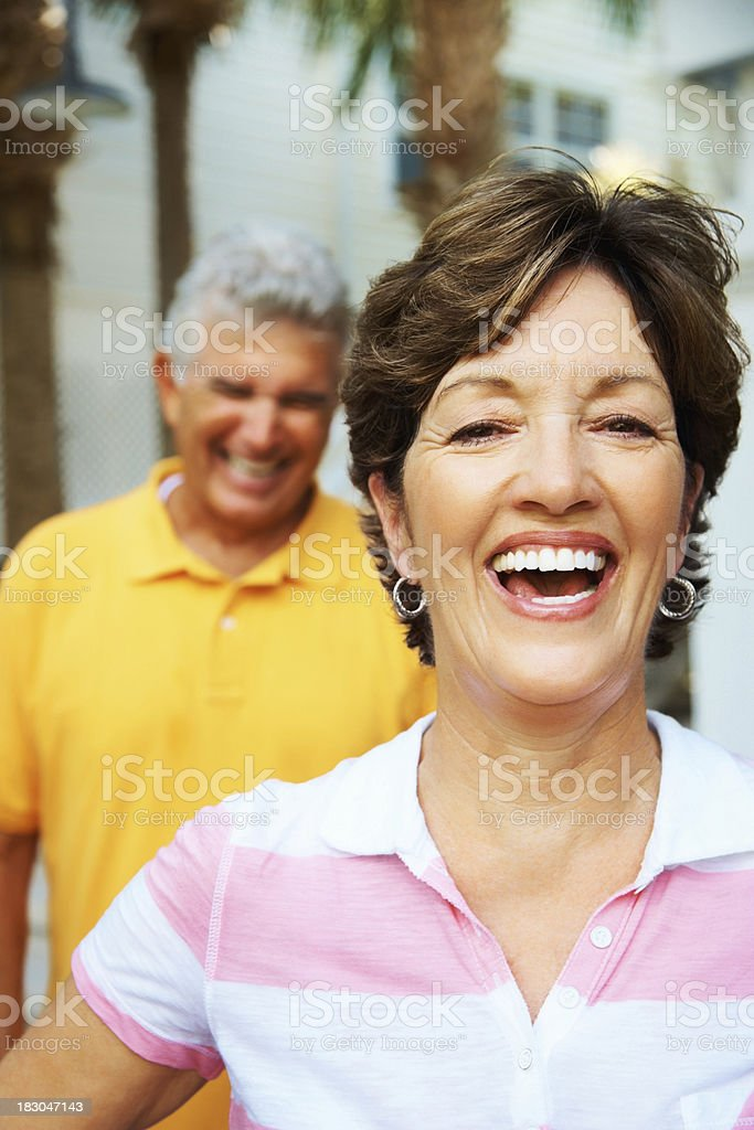 Cheerful woman laughing with a senior man in the background royalty-free stock photo