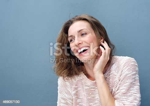 istock Cheerful woman laughing with hand in hair 469057130
