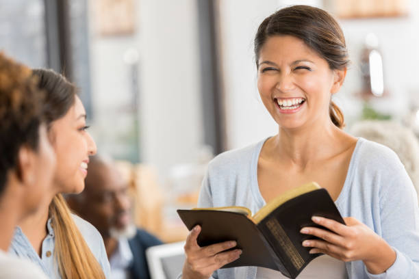 Cheerful woman leads Bible study Cheerful mid adult woman discusses the Bible with young women. She is mentoring the young women. They are meeting in a busy coffee shop. clergy stock pictures, royalty-free photos & images